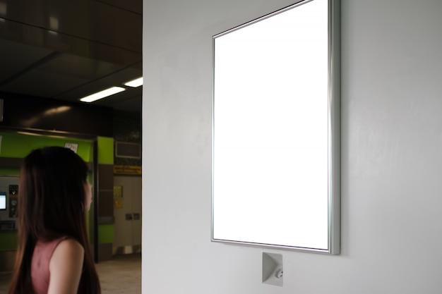 Traveller woman looking at blank advertising billboard at subway station. Premium Photo