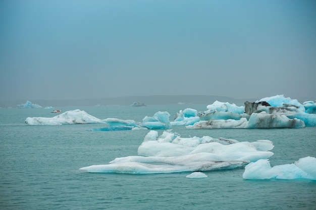 Travellers take a boat to see the floating ice in the ocean icebergs in jokulsarlon glacier lagoon, iceland Premium Photo