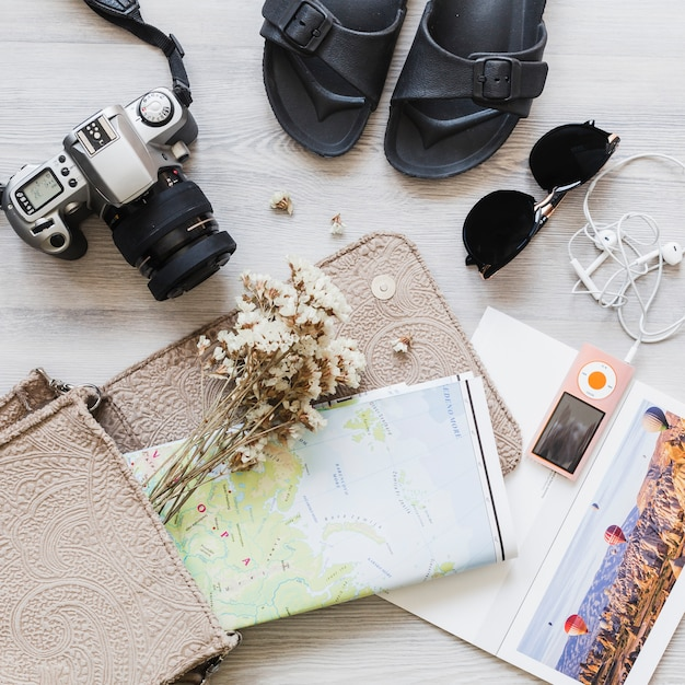 Travelling accessories with map and flower in the handbag over the desk Free Photo