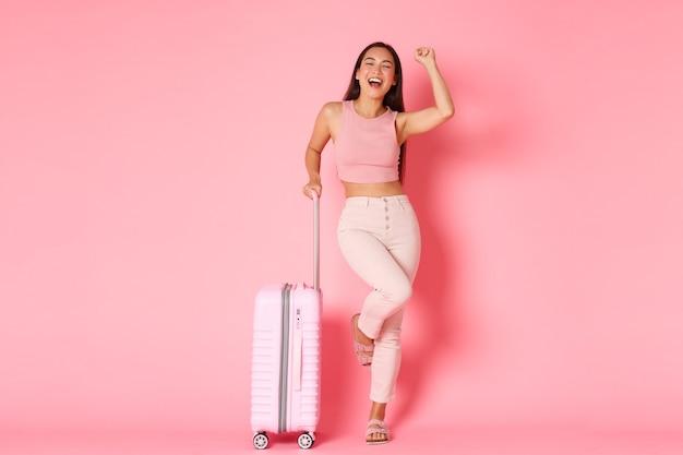 Viaggi, vacanze e concetto di vacanza. il turista spensierato della ragazza asiatica di successo è arrivato all'aeroporto con la valigia Foto Gratuite