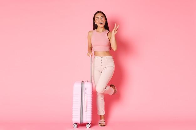 Viaggi, vacanze e concetto di vacanza. allegra ragazza asiatica in abiti estivi confezionato borse per viaggi all'estero Foto Gratuite