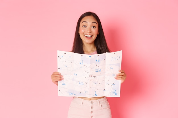 Travelling, lifestyle and tourism concept. cheerful, attractive asian girl tourist explore new city, visiting museums, showing map of city with sightseeings and smiling upbeat, pink background. Free Photo