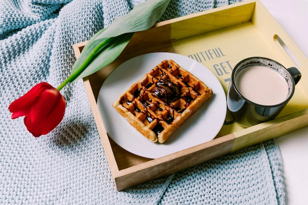 Tray with belgian waffle and cup of milk on scarf Free Photo