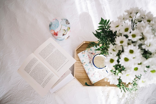 Tray with bouquet near opened book Free Photo