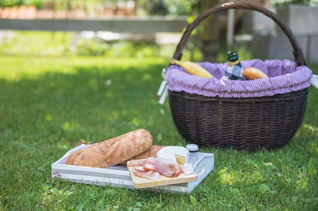 Tray with bread; bacon; cheese and basket in park Free Photo
