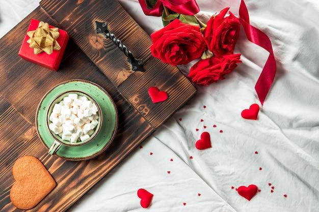 침대와 꽃, 낭만적 인 아침 식사 개념에 커피 컵 트레이 프리미엄 사진