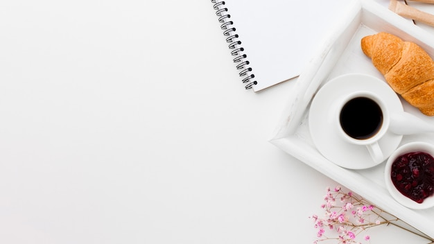 Tray with cup of coffee and croissant beside notebook Premium Photo