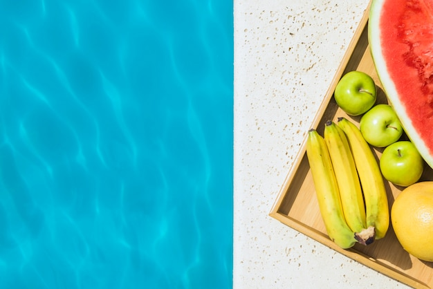 Tray with fruits placed on pool edge Free Photo