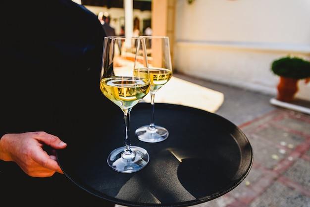 Tray with two glasses of champagne held by a waiter. Premium Photo