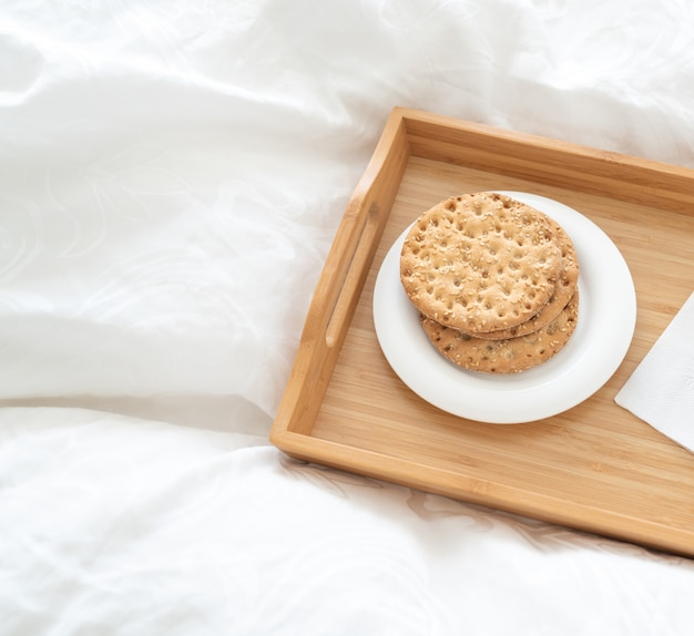 Tray with water and crackers dbreakfast on a bed Premium Photo
