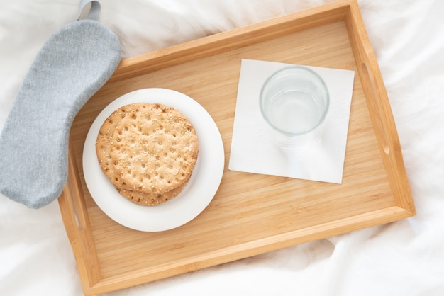 Tray with water and crackers dibreakfast on a bed Premium Photo