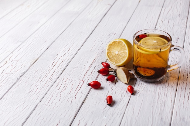 Treating cold. hot tea with lemon and berries stands on white wooden table Free Photo