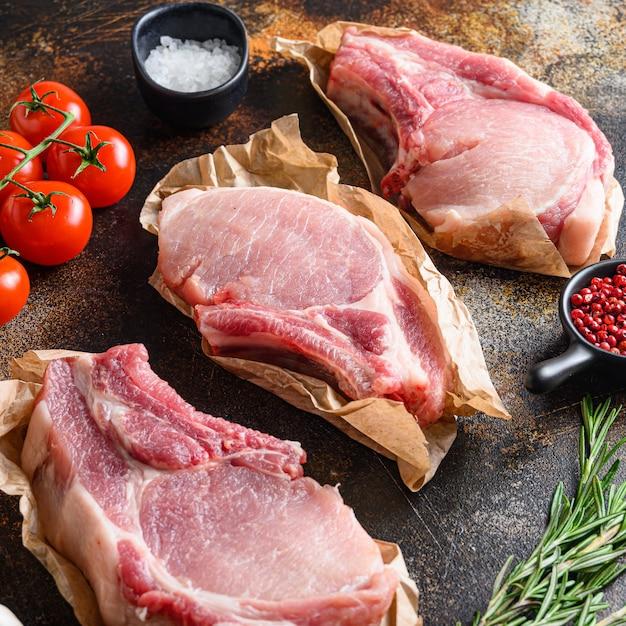 Гроздь сырых свиных отбивных с травами, маслом и специями Premium Фотографии