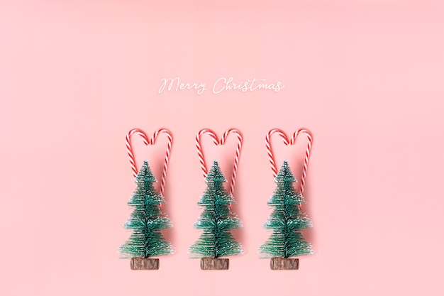 Tree Christmas tree with candy cane hanging on pastel pink wall with ...