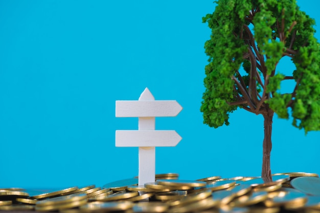 Tree growing on pile of golden coins and white wooden board sign, Premium Photo