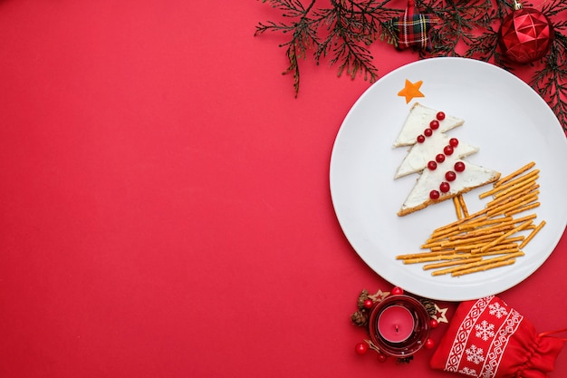 Tree made from bread with cream cheese decorated with berries on a white plate on red background. Premium Photo