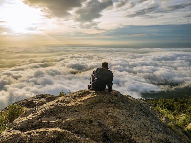 Trekker sitting on the mountain with beautiful sunrise and sea of mist in the morning on khao luang mountain in ramkhamhaeng national park,sukhothai province Premium Photo