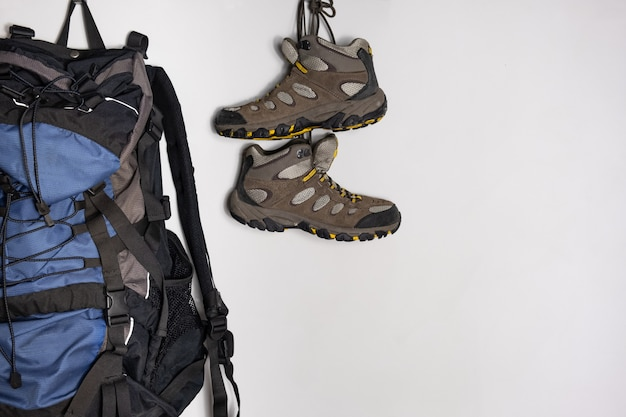 Trekking boots and a tourist backpack on white background. preparing for a hiking trip concept. Premium Photo