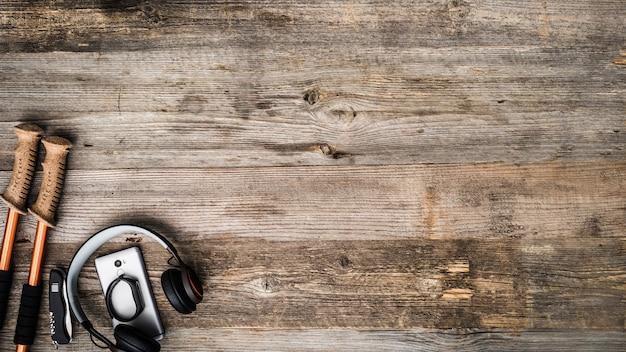 Trekking pole, mobile phone and headpnones on wooden background Premium Photo