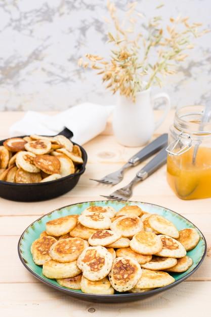 Тренд завтрак. голландские мини блины на тарелку и сковорода с ними на деревянном столе. Premium Фотографии