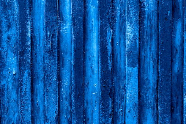 Trend color 2020 classic blue,  peeled wooden fence background for design. Premium Photo