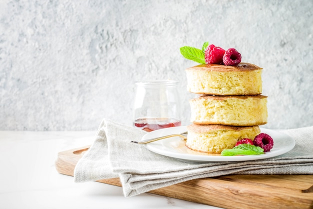 Trendy asian food, fluffy japan souffle pancakes, hotcakes with maple syrup and raspberry light concrete table Premium Photo
