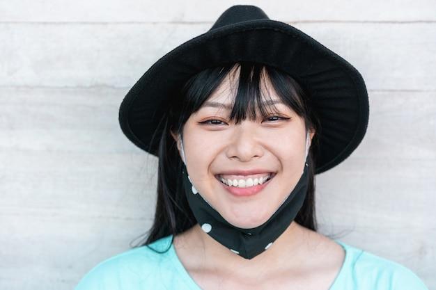 Модная азиатская девушка улыбается в защитной маске во время вспышки коронавируса Premium Фотографии