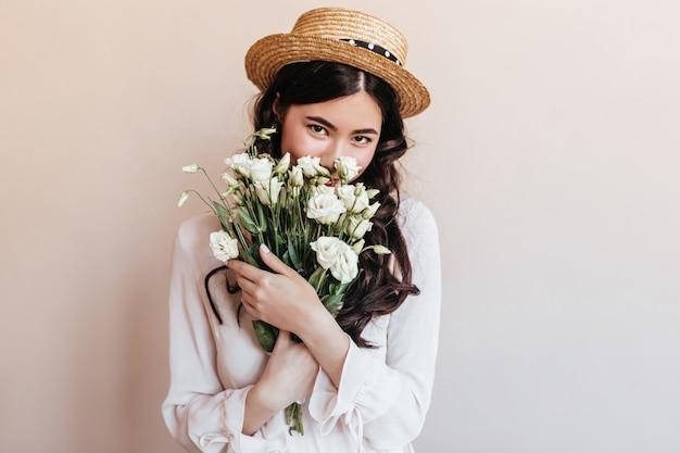 花を嗅ぐトレンディなアジアの女性。白いトルコギキョウの花束を保持しているロマンチックなブルネットの若い女性。 無料写真