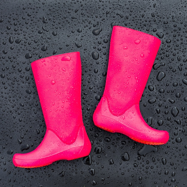 Trendy bright pink rubber boots on black wet surface covered with raindrops Premium Photo