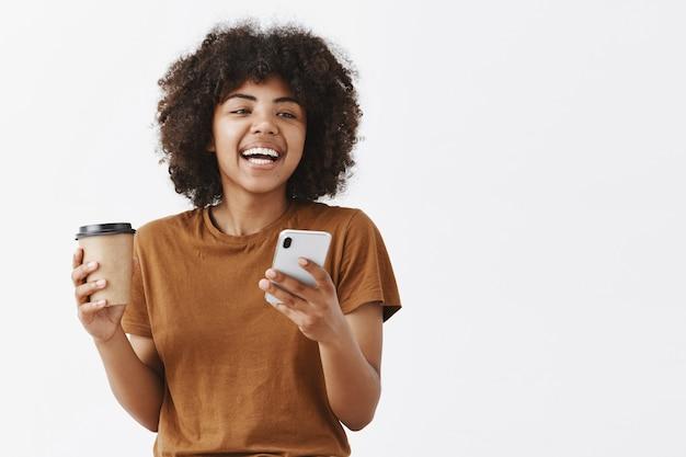 Модная беззаботная афроамериканка с кудрявыми волосами в коричневой футболке смеется, разговаривая с друзьями, пьет кофе из бумажного стаканчика и держит смартфон Бесплатные Фотографии