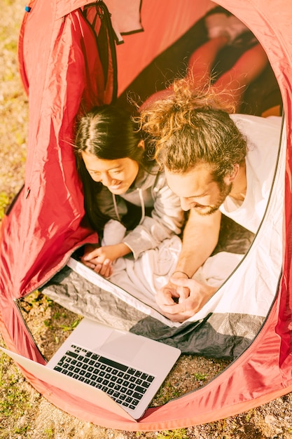 Trendy couple relaxing in tent with laptop Free Photo