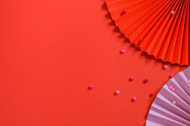 赤の背景にトレンディな環境にやさしい紙のファンと豆。グリーティングカード、パーティの招待状、その他の目的に最適なデザイン。上面図、モックアップ写真。 diyのコンセプト。 Premium写真