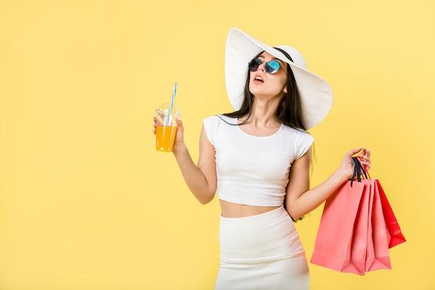 カクテルや買い物袋を持つトレンディな女性 Premium写真