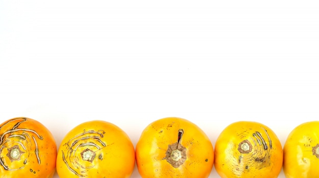 Trendy large ugly organic yellow tomatoes on a white background Premium Photo