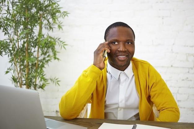 電話で会話し、開いているラップトップの前に座って、彼の旅行ブログのコンテンツに取り組んでいるトレンディな外観の暗い肌の男性ブロガー。人、仕事、職業、そして現代の電子機器 無料写真
