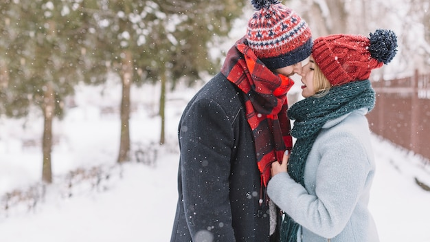 Trendy loving couple kissing in snowfall Free Photo