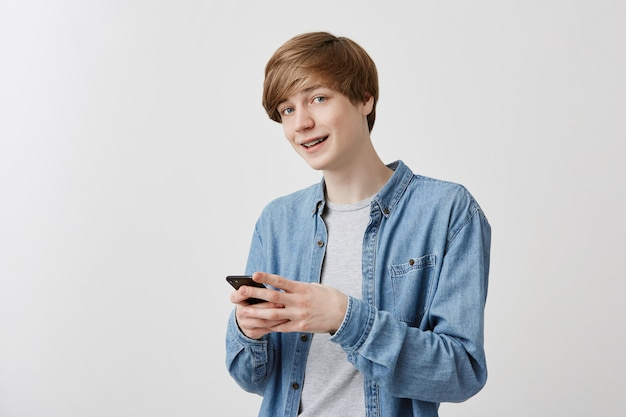 屋内で携帯電話を使用してポーズをとったり、友達とチャットしたり、メッセージを入力したりするデニムシャツに金髪と青い目をしたトレンディな男性。笑顔で見ている、現代の技術を使用している賢い学生 無料写真