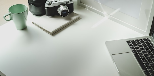 Trendy photographer workplace with tablet and vintage camera Premium Photo