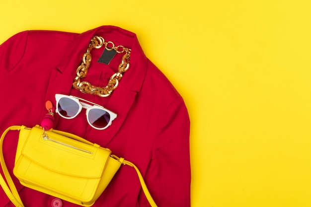 Trendy woman outfit with accessories on bright yellow background Premium Photo