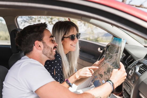 Trendy young couple sitting inside the car looking at map Free Photo