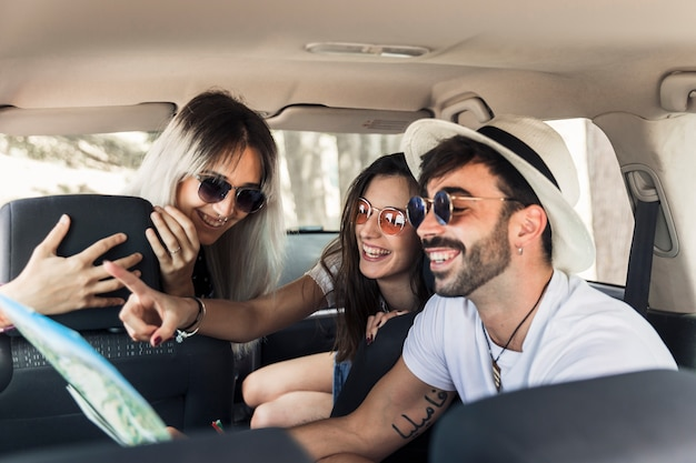 Trendy young friends sitting inside the modern car looking at map Free Photo