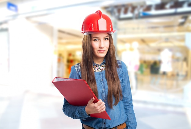 Trendy young woman holding a red folder and wearing a helmet Free Photo