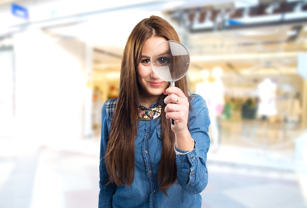 Trendy young woman with a magnifying glass in front of her eye Free Photo