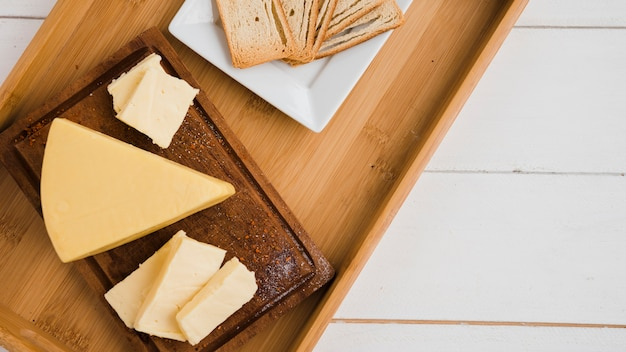 Triangular cheese wedges on wooden tray against white desk Free Photo