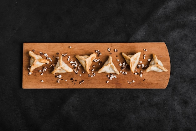 Triangular dumplings on wooden tray over the black background Free Photo