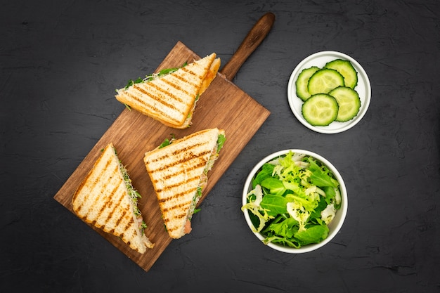 Triangular sandwiches on chopping board with salad and cucumber slices Premium Photo