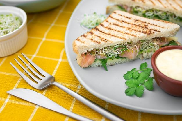 Треугольные бутерброды на тарелке с майонезом и столовыми приборами Бесплатные Фотографии
