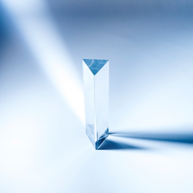 Triangular transparent prism with shadow on blue backdrop Free Photo