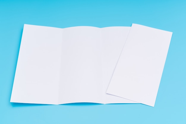 Trifold white template paper on blue background . Free Photo