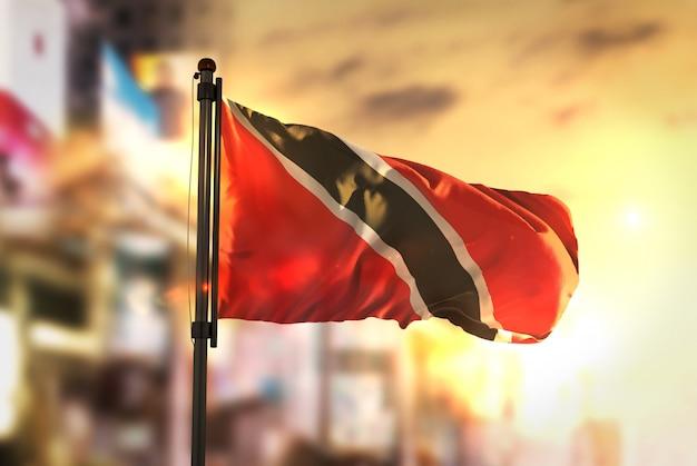 Trinidad and tobago flag against city blurred background at sunrise backlight Premium Photo